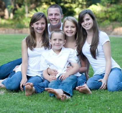 Five children sitting on grass in jeans and white t-shirts