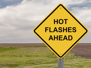 Caution sign with hot flashes ahead painted on it
