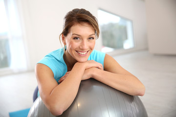 Over 40 woman smiling with arms crossed over a grey stability ball