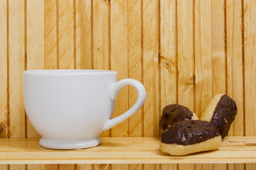 Mini eclairs and a white mug on a wooden backdrop