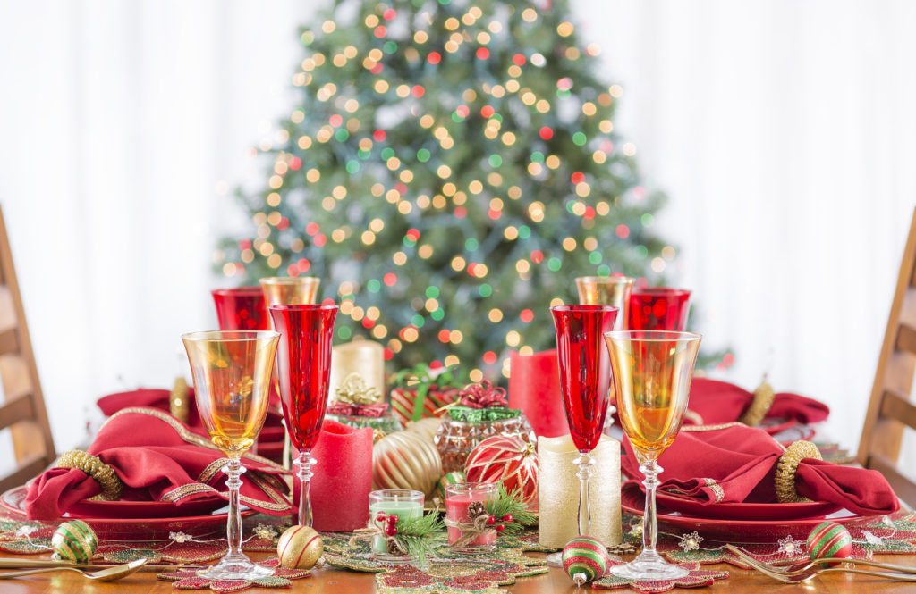 Christmas dinner set with golden and red candles and plates. Christmas tree lights bokeh is in the background. Christmas dinner table ideas.