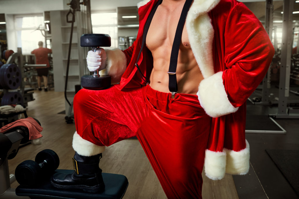Santa Claus with dumbbells in the gym close-up on Christmas.