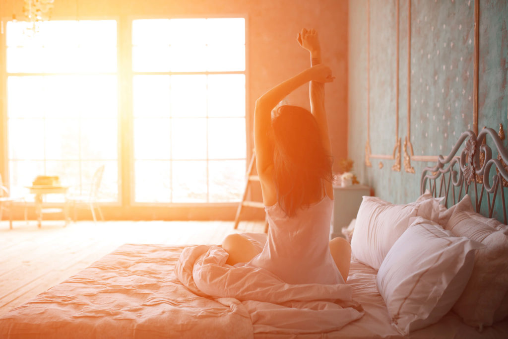 Woman stretching after waking up after sleep